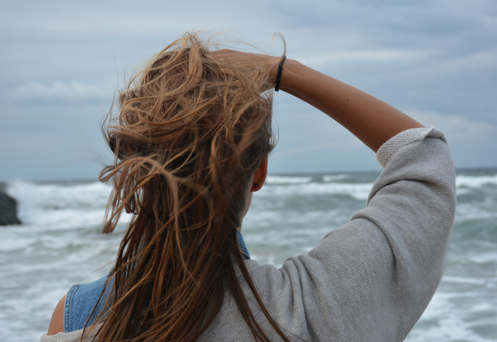 Woman staring at the ocean running her hand through her hair