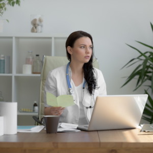 Doctor sitting in office with laptop open