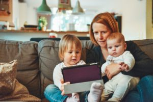 Mother sitting on couch with her two kids looking at iPad