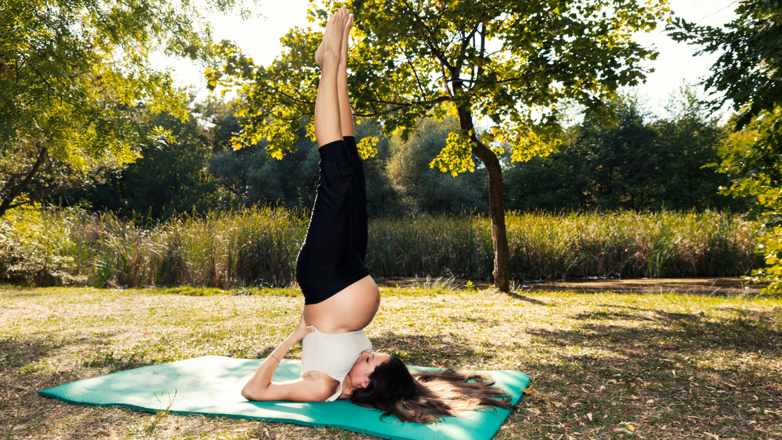 Surrogate doing yoga in nature on a turquoise yoga mat