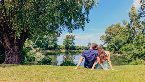 Couple peacefully sitting on grass field in front of a lake