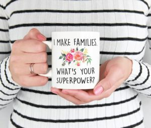 """Woman holding coffee mug that says """"I make families. What's your superpower?"""""""