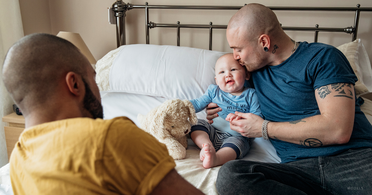 Two gay parents play with their baby on a bed.
