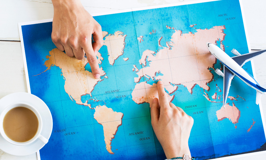 Two hands point to different places on a world map.